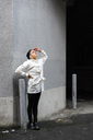 Young woman in white coat standing by wall and looking up - FOLF02969
