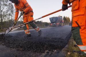 Three manual workers repairing road - FOLF03248