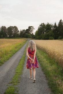 Rear view of woman walking along dirt road in summer - FOLF03359