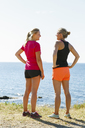 Two young women in sports clothing standing on seaside - FOLF03503