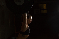Young woman lifting barbell in gym - FOLF03572