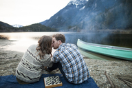 Young couple kissing while sitting on picnic blanket at lakeshore - CAVF30876