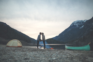 Full length of young couple holding hands while kissing at lakeshore against mountains during dusk - CAVF30879