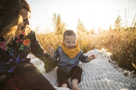 Mother looking at happy son sitting on picnic blanket at field - CAVF30900