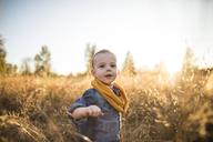 Cute baby boy standing on field against sky - CAVF30903