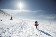 Rear view of woman walking on snow covered field against sky on sunny day - CAVF31110