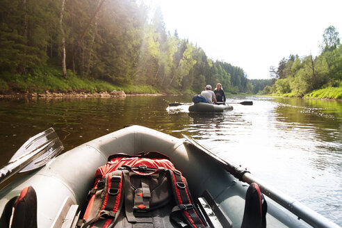 Couple traveling on inflatable boat in river during summer - CAVF31140