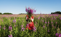 Female farmer hiding face with flowers on farm against clear blue sky - CAVF31149
