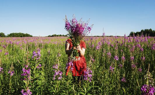 Female farmer hiding face with flowers on farm against clear blue sky - CAVF31149