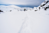 Distant view of hiker on snow covered mountain against sky - CAVF31158
