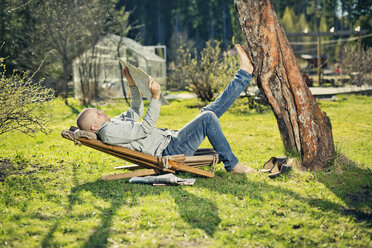 Mid adult man reading newspaper on sunlounger - FOLF03612