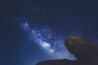 Man standing on rock in Joshua Tree National Park and looking at Milky Way - FOLF03633