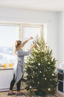 Woman decorating christmas tree - FOLF03648