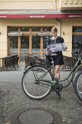 Young woman in Berlin with city map and city bicycle - FOLF03669