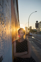 Portrait of young woman leaning against wall in Berlin - FOLF03672