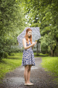 Woman wearing floral dress standing with umbrella in park - FOLF03684