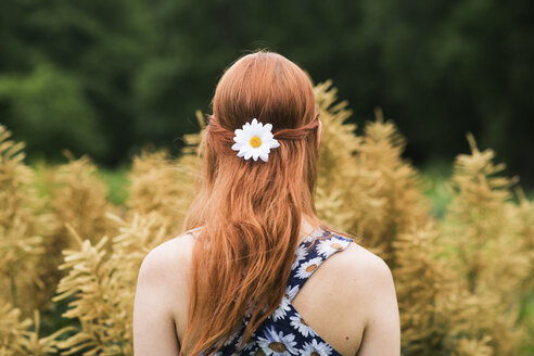 Young woman wearing floral dress and daisy flower in her hair - FOLF03687