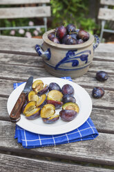 Fresh plums in stoneware pot and chopped plums on plate - GWF05475
