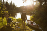 Man by canoe on riverbank - FOLF03879