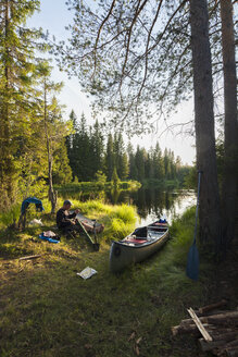 Man sitting by canoe on riverbank - FOLF03882