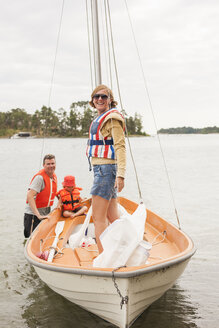 Family with child wearing life jackets on sailboat on river - FOLF03897