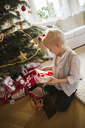 Little blonde boy checking Christmas presents sitting on floor - FOLF03903