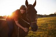 Portrait of smiling woman on horse at sunset - FAF00082