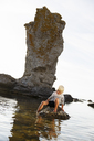 Blonde little boy sitting on rock with one leg in water - FOLF04155