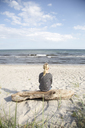 Mature woman sitting on driftwood and looking at sea - FOLF04209