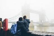 Mid adult man holding boy while looking at Tower Bridge in London in fog - FOLF04299
