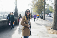 Smiling woman standing on pavement at Victoria Embankment in London - FOLF04302