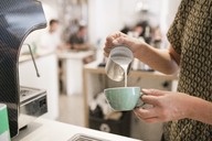 Woman pouring milk into coffee cup in Portugal - FOLF04413