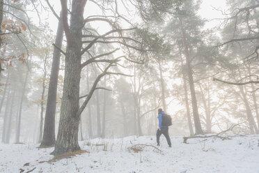 Man walking through a snowy forest - FOLF04788