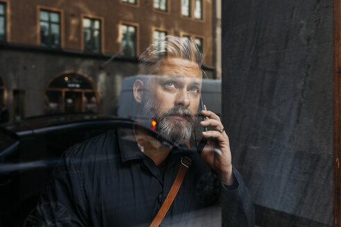 Man on smart phone through window - FOLF04845