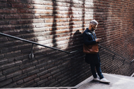 Man beside brick wall on smart phone - FOLF04848