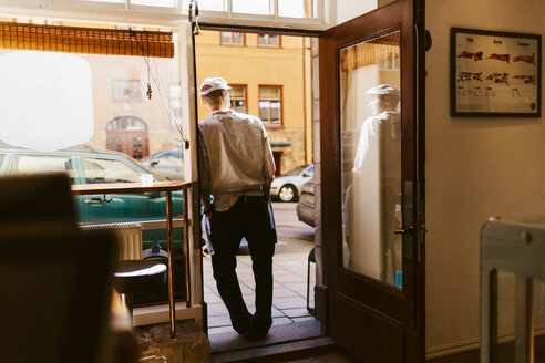 Rear view of butcher leaning on doorway of store - FOLF04941
