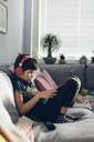 Boy with headphones sitting on sofa - FOLF05115