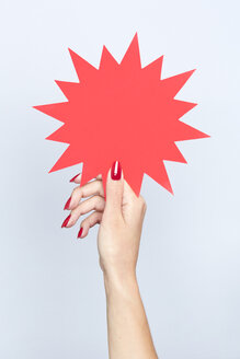 Close-up of woman's hand holding a blank jagged sign - SRYF00778