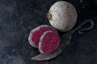 Whole and sliced beetroot and an old knife on dark metal - CSF29015
