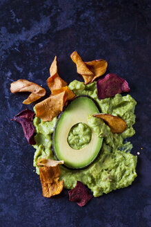 Guacamole, slice of avocado and vegetable chips on dark ground - CSF29030