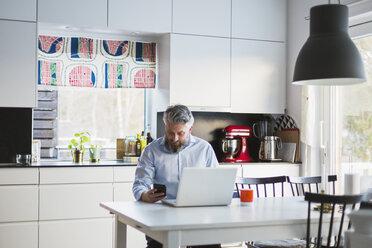 Man with laptop in kitchen - FOLF05220