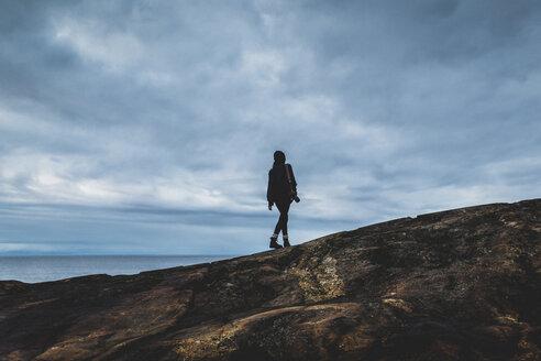 Woman on rocky coastline in Vasterbotten, Sweden - FOLF05262