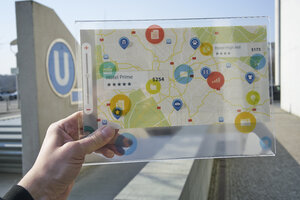 Hand holding futuristic device with digital icons and map in the city - FMKF05018