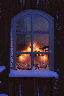Lit window of Skagershult Church with snow - FOLF05508