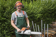 Portrait of smiling man wearing protective clothes holding motor saw - PAF01787