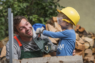 Playful father and son with toy saw - PAF01790
