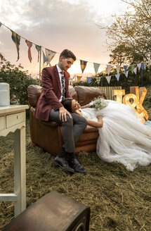 Bride lying over sofa with groom in the field - DAPF00928