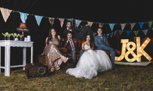 Portrait of wedding couple with friends on sofa on a night field party - DAPF00931