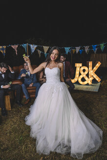 Happy bride holding cocktail glass on a night field party with groom and friends in the background - DAPF00934
