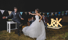 Happy bride and man dancing on a night field party - DAPF00937